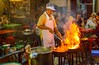 Heatwave (Robica Photography) Tags: thailand bangkok evening cook cooking fire wok frying people streetphotography outdoor kitchen restaurant hot sitting colourful dinner food pan tables street d3200 steam smoke robicaphotography art streetart