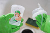 Hand washing sippy cup in green rubber gloves and soapy sponge in kitchen sink with lid off and straw (yourbestdigs) Tags: sippy cups sip sips cup kids childs baby cleaning washing handwashing hands gloves rubber green sink sponge soap straw nuspin zoomi
