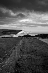 The Seven Sisters (Lloyd Austin) Tags: coastguardcottages nikon d7200 sigma1750mm monochrome mono blackandwhite blackwhite bnw overcast people fields pathway coast coastline coastal shoreline proud majestic moody dramatic exposure contrast grey white black sussex englishchannel rocks water grass fence cliffs chalk view vista iconic sky cloudscape seascape landscape england cuckmerehaven sevensisters
