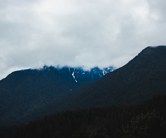 snow peeks out from under clouds (Dylan Bretz) Tags: canon t3i photoshop lightroom vancouver canada british columbia pacific northwest clouds overcast snow mountains forest