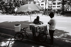 Something Sweet (D. R. Hill Photography) Tags: bangkok thailand asia southeastasia city urban street streetphotography streetfood food blackandwhite monochrome grain 135 35mmfilm analog contax contaxg1 g1 carlzeissbiogon28mmf28 zeiss biogon 28mm primelens fixedfocallength wideangle kodak kodakfilm kodaktrix400 trix