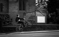 Emmanuel wheelie (Chilanga Cement) Tags: fuji fujix100f fujifilm xseries x100f 100f bw blackandwhite monochrome bike bikes bicycle boy kid wheelie trick church methodism methodist school uniform ormskirk westlancashire lancashire sign signs