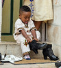 """Reverse Cinderella: """"There are so many pairs of shoes by the door of the (Ethiopian) Church; one of them will surely suit."""" (ybiberman) Tags: israel jerusalem ethiopianchurch ethiopiancathedral wedding boy sitting shoes puttingonshoes stickouttongue tonguedoorportraitcandidstreet photography people"""
