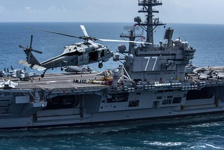 An MH-60S Sea Hawk helicopter flies next to USS George H.W. Bush.
