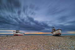 Sunrise at Dungeness, Kent (MelvinNicholsonPhotography) Tags: dungeness kent seaside seascape boats sunrise sky clouds longexposure pebbles beach orange blue