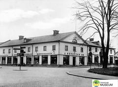 tm_7476 - Centralplatsen, Tidaholm (Tidaholms Museum) Tags: svartvit positiv tidaholm byggnad exteriör affärsbyggnad vägvisare