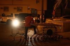 Carrefour Parking (N A Y E E M) Tags: man trolley latenight light availablelight atmosphere mood carpark street carrefour supermarket medina almadinah ksa saudiarabia