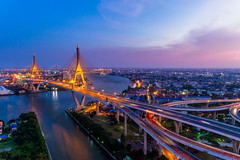 Aerial view of Bhumibol suspension bridge in Bangkok city with light trails of car on the road at sunset sky and clouds in Bangkok Thailand. (MongkolChuewong) Tags: aerial architecture art asia auto bangkok bay bhumibol bhumipol bridge building car chaophrayariver chaoprayariver city cityscape connect connection curve downtown drive drone dusk evening expressway freeway highway industry landmark landscape lane lighttrails motorway night panorama panoramic river roads route sunrise sunset suspension thailand traffic transport twilight urban view vision way tambonbangyo changwatsamutprakan th