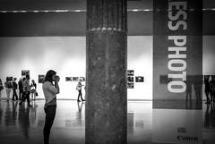 Desiderio di un clic (o.solemio) Tags: photo n°448 minoosolemio ragazza fotografa museo mostra foto persone sala colonna wpp monocromo bianconero leicavlux