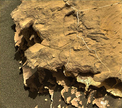 Holes in a Layered Rock, variant (sjrankin) Tags: 21may2018 edited nasa mars msl curiosity galecrater 2052mr0108750010903440e01dxxx rock layers lightcolored holes laserholes sand