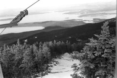121169 14 (ndpa / s. lundeen, archivist) Tags: nick dewolf nickdewolf december photographbynickdewolf winter greenville maine mooseheadlake snow blackwhite bw 1969 1960s monochrome blackandwhite skitrip bigsquaw bigsquawmountain bigsquawmountainresort 35mm film chairlift skiing skier people trails slopes view lake island islands mooseisland blacksandisland lift trees snowcovered cable cables hills
