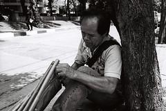 Beretta (D. R. Hill Photography) Tags: bangkok thailand thai asia southeastasia urban city vendor amulet buddhist buddhism blackandwhite monochrome grain 135 35mmfilm man portrait environmentalportrait street streetphotography analog contax contaxg1 g1 carlzeissplanar35mmf2 planar 35mm primelens fixedfocallength zeiss film kodak kodakfilm kodaktrix400 trix