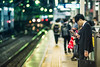 Station Platform (Jon Siegel) Tags: nikon nikkor d810 135mm f2 135mmf2dc 135mmf2 man phone businessman salaryman train station platform japan japanese tokyo night bokeh evening lights bright city urban street candid