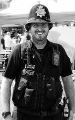 Policing the pirates. (Neil. Moralee) Tags: neilmoralee piratebrixhamneilmoralee police man policeman force 640 devon cornwall devonandcornwall young face portrait street candid taser radio stab vest stabvest helmat brixham uk patrol beat walking bright sunshine hot stubble beard pirate festival 2018 law order justice enforce black white bw bandw blackandwhite work working bobby cop copper fuzz smile smiling uniform crime neil moralee nikon d7200