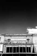 """here i sit alone (listening to """"empty as a drum"""", turnpike troubadours) (haint_blue) Tags: cloud sky bw blackandwhite monochrome smalltown southern country cocacola sign rural fiveanddime mississippi hickory"""