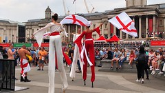 Patriotic stilt walkers - Feast of St George, Trafalgar Square, London (edk7) Tags: olympusomdem5 edk7 2018 uk england london trafalgarsquare feastofstgeorge festival nationalgallery people person male female stiltwalker performer patriotic flag dome column architecture building oldstructure museum city cityscape urban life