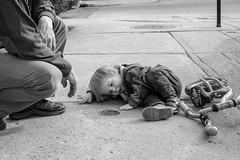 L'observation d'un trou... (Nicojuli) Tags: noiretblanc blackandwhite enfant rue trottoir