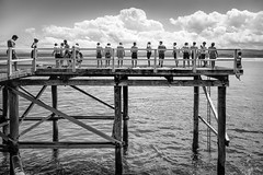 the plunge (andrewlance photography) Tags: 28mm asph australia elmaritm frisbee fyshwickunited lr5 leica leicammonochrom lightroom5 merimbula nd nsw newsouthwales silverefexpro2 ultimate ultimatefrisbee andrewlancecom bw blackandwhite blackwhite bnw bondingweekend boys clouds dive f28 jetty jump leap men monochrome monocrome myflickr neutraldensityfilter ocean old plunge sea sky sun surf swim team together warf water wood