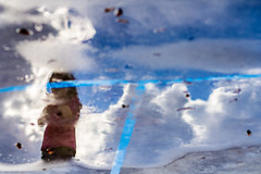 Juego de reflejos III (Carlos Larios - Fotolarios) Tags: jugar parque niña nube lluvia charco columpio kid girl water agua clouds sky game reflection florr park rain upsidedown street streetphoto