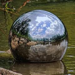 Orb Adrift (clarkcg photography) Tags: orb reflection reflector stainlesssteel shine grainy landscape water river oklahoma arkansasriver globe ball sphere cof023 florareflection cof23patr cof023mari cof023dmnq