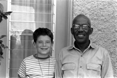 042168 34 (ndpa / s. lundeen, archivist) Tags: nick dewolf nickdewolf photographbynickdewolf 1968 1960s bw monochrome blackwhite blackandwhite 35mm film april neworleans louisiana lemlehouse lemlehome child boy alexander man black africanamerican unidentified staff staffmember glasses eyeglasses smile smiling sambynum