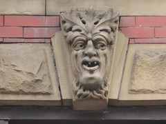 Three Tooth Gargoyle 2738 (Brechtbug) Tags: green man three teeth face gargoyle above window building facade 9th avenue west 52nd street nyc 05202018 new york city midtown manhattan 2018 gargoyles portraits monster portrait monsters creature faces spooky art architecture sculpture keystone mask brownstone brown stone capital may spring sneer sneering satyr tooth
