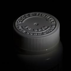 A cover-up -[ HMM ]- (Carbon Arc) Tags: macromondays lowkey black white dark medicine drug bottle jar cap cover lid childresistant instructions