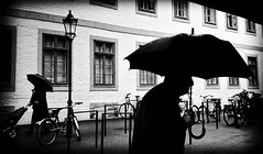 Under the weather. (Mister G.C.) Tags: street urban photography blackandwhite bw yashica yashicaautofocusmotor compactcamera pointshoot 38mm f28 primelens autofocus streetphotography urbanphotography shot image photograph candid people monochrome silhouette umbrella rain raining rainy town city analog analogphotography 35mm film schwarzweiss strassenfotografie mistergc germany niedersachsen lowersaxony deutschland europe