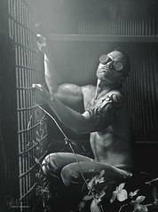 The Passion and Addiction of the Gollum (Philip Bonneau) Tags: blackandwhite blackandwhitephotography portrait man male shirtless tattoo goggles poisonivy caged trapped metal latin latino