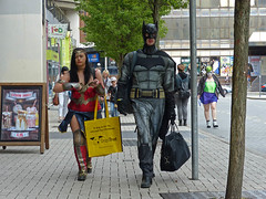 Exit the superstore (Andy WXx2009) Tags: people outdoors candid streetphotography walking pavement bags cardiff wales europe shopping batman cosplay woman man girl boots femme female brunette mask costumes comicon style fashion sexy beauty superhero
