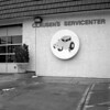servicenter (kaumpphoto) Tags: servicecenter rolleiflex 120 tlr ilford car auto automobile roof shingles pot glass cement concrete stucco plant shrub door light flame tire round circle bw black white minneapolis letters apostrophy service garage illustration cartoon fix repair