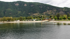 Shuswap Lake and Sicamous Public Beach from the Rocky Mountaineer enroute Kamloops to Revelstroke, British Columbia, Canada (Black Diamond Images) Tags: revelstroke lake banff alberta canada kamloops canadian rockies tourism train railroad railway travel photography landscapes mountain mountainside landscape water britishcolumbia lakelouise kamloopstobanff rockymountaineer rockymountaineerroute canadianrockies canadiantourism armstronggroupltd goldleaf goldleafdomecoach travelphotography bridge beach redfootbridge sicamouspublicbeach sicamousbeach sicamous shuswaplake maralake