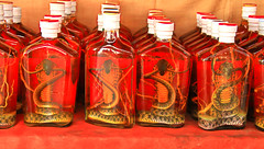 Snake Wine (Chandana Witharanage) Tags: laos snakewine alcoholicbeverage drink lifeisarainbowoneyearincolours red 2252weeks bottle glassbottle canoneos7d canonefs18200mmf3556is photographedbychandanawitharanage crossedmekongriver