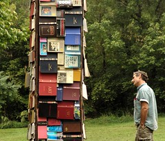 tower of books and a man interested (by zen)