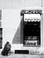 Gloves (Feldore) Tags: florence italian italy man candid elderly hat outside shop sitting street sunshine gloves shadow santa croce
