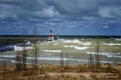 A bolt of sunlight on a cloudy day (mswan777) Tags: tree sky cloud scenic lake michigan seascape pier lighthouse beach sand shore coast storm wave wind nikon d5100 nikkor 1855mm crash blue red spring