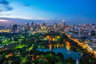 Sunset scence of Bangkok modern office buildings and condominium in Bangkok city downtown with sunset sky and clouds at Bangkok , Thailand. Lumpini park