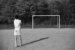 Poudrière. (theodirector) Tags: football foot footballer soccer calcio soccerplayer young youth child childhood alone lonely blackandwhite goal littleboy allalone daylight stadium stage back silhouette backportrait kid looking thinking noiretblanc geometric geometry littleman youngman footballcage cage white sand vincennes boisdevincennes playing playingfootball sport footballlover dreamer soccerfield footballfield frenchboy paris shadow monochrome streetphoto streetphotography streetreport