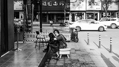 Ladies (Go-tea 郭天) Tags: hangzhoushi zhejiangsheng chine cn linan hangzhou mother daughter child children family love 2 together care woman girl ladies connexion sidewalk seat seated roads cars rest resting sun sunny shadow young youth mobile phone cell cellular cellphone data network addiction street urban city outside outdoor people candid bw bnw black white blackwhite blackandwhite monochrome naturallight natural light asia asian china chinese canon eos 100d 24mm prime chair pavement