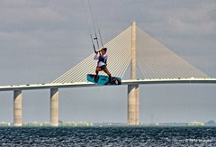 Flying High by the Sunshine Skyway (pandt) Tags: kite boarder kiteboarding sunshineskyway beach fortdesoto desoto pinellas water ocean sea bay tampabay bridge flickr action florida flying sky clouds canon eos slr 7d