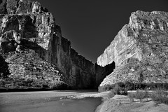 A Canyon and River to Separate Two Countries and Create a Border (Black & White) (thor_mark ) Tags: blackwhite nikond800e day5 triptobigbendnationalpark bigbendnationalpark cliffwalls desertlandscape sierraponcecliffs usbiospherereserve usmexicanborder santaelenacanyon lookingsw capturenx2edited colorefexpro desert desertplantlife desertmountainlandscape outside nature landscape sunny blueskies mountains mountainsindistance mountainsoffindistance mountainside hiketosantaelenacanyon santaelenacanyontrail riogrande river trees chihuahuandesert lookingintomexico rivercanyon 1500feethigh intermountainwest southwestbasinsandranges transpecostexasranges bigbendranges westbigbendranges ca–—ndesantaelena protectedareaoffloraandfaunasantaelenacanyon sierramadreoriental alongbanksofriogrande project365 portfolio mesadeanguilla limestonecliffs tx unitedstates cañóndesantaelena