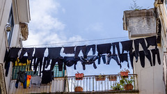 An exaggeration of clothes hanging out. ((Paolo P)) Tags: napoli naples italia italy pannistesi laundry cielo sky nuvole clouds