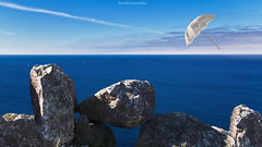 Una sombrilla de altos vuelos - An umbrella of flying high (ricardocarmonafdez) Tags: seascape cielo sky blue azul imagination edition composition depth sunlight shadows vanishingpoint light concept rocas rocks sombrilla umbrella 60d 1785isusm canon