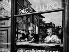 Northern Quarter 212 (Peter.Bartlett) Tags: manchester niksilverefex women window unitedkingdom restaurant people city olympuspenf peterbartlett woman urban eating monochrome uk m43 couple streetphotography cafe microfourthirds sign blackandwhite candid bw england gb