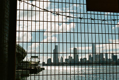 """""""cage"""" (180506) (hugo poon - one day in my life) Tags: nikonfe2 nikon50mm18 kodak film kodakportra400 hongkong northpoint northpointferrypier tsimshatsui icc masterpiece victoriadockside victoriaharbour easterncorridor skyscrapers skyline cloud sky caged barbedwire city sunny sunday afternoon"""