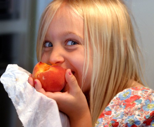 Grayson, our granddaughter, eating a Georgia peach and enjoying every bite.