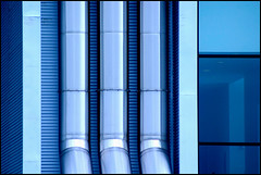 blue tubes ( marc_l'esperance) Tags: blue windows light abstract detail reflection building texture geometric glass lines vertical metal vancouver contrast canon reflections dark eos geometry abstractart  tubes shapes angles ubc 2006 shades architectural textures 10d round forms abstraction straight cylinders allrightsreserved gradients cml gvrd universityofbritishcolumbia canonef100300mmf56 flickrjobdiff